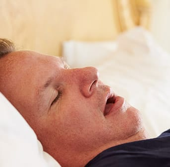 man sleeping in bed with mouth open
