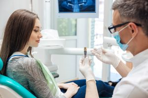 Dentist showing patient dental implant
