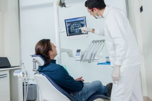 dentist showing patient dental x-rays