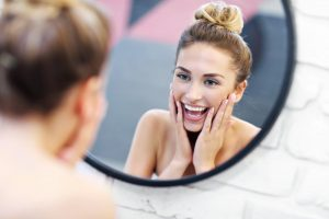 Young woman smiling in the mirror