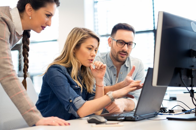 woman working on computer with coworkers